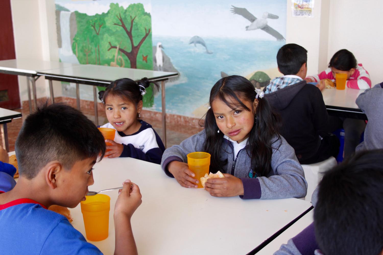 Kinder aus Ecuador sitzen im Tagesheim am Tisch und essen und trinken etwas.