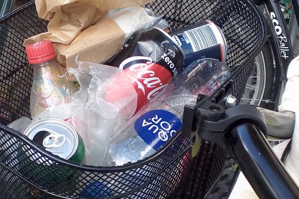 Ein mit leeren Plastikflaschen gefülltes Velokörbchen.