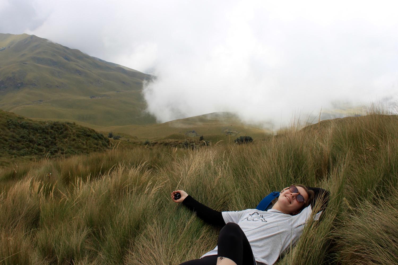 Frau mit weissem T-Shirt und Sonnenbrille liegt in hohem Gras. Im Hintergrund sieht man ein Hügel und Nebelschwaden, die hervorkommen.