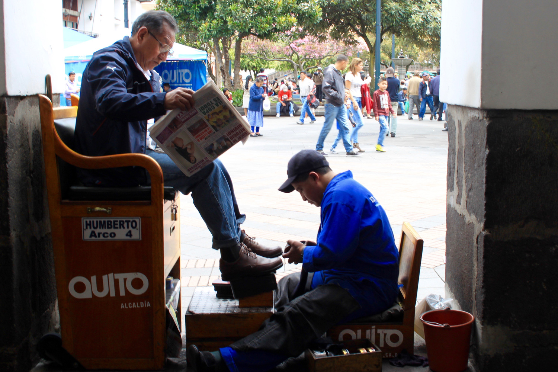 Ein Schutzputzer sitzt auf einem kleinen Stuhl. Links von ihm auf einem erhöhten Stuhl sitzt ein Kunde, der die Zeitung liest und sich die Schuhe putzen lässt.