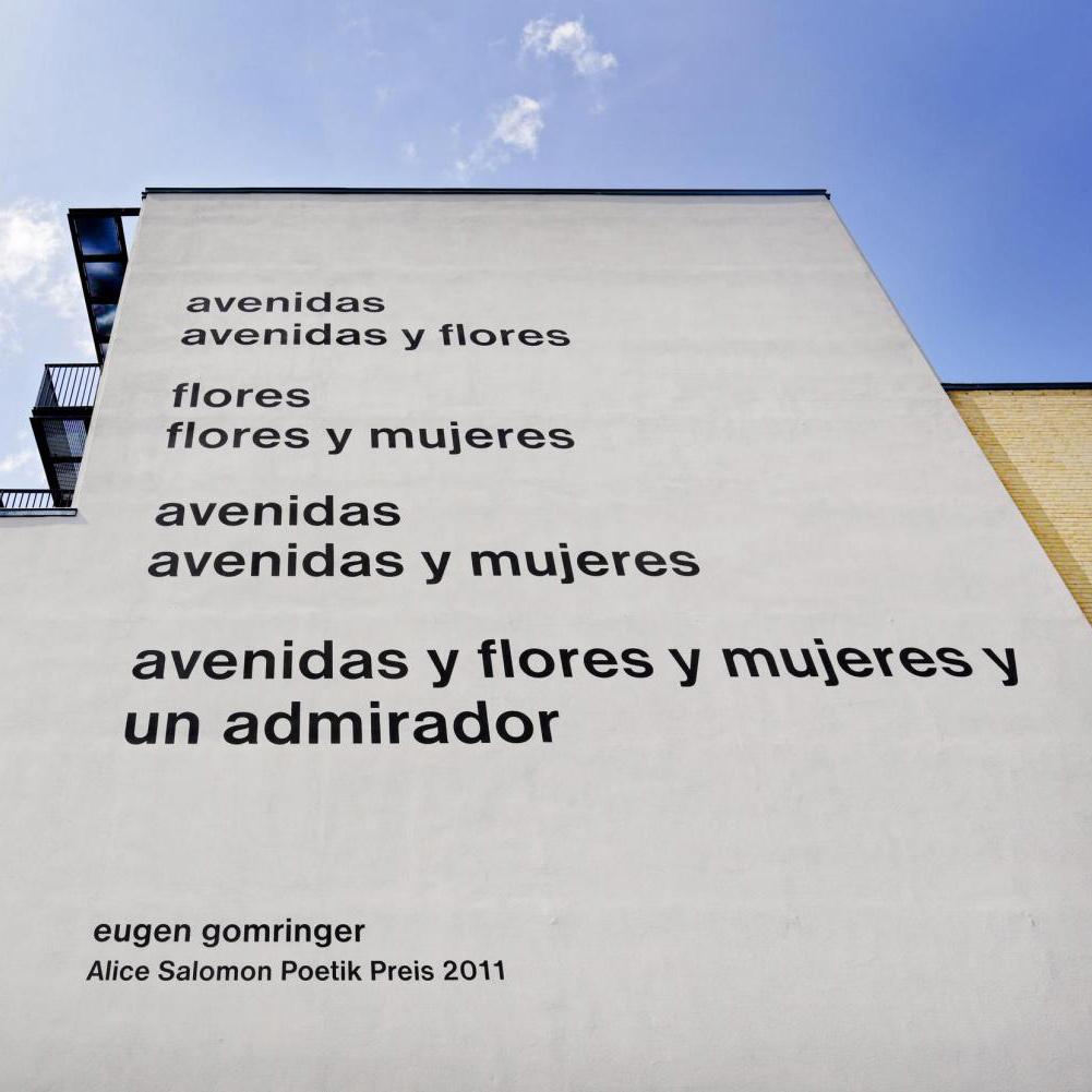 Spanisches Gedicht an einer beigen Hausmauer. Der Autor ist Eugen Gomringer.