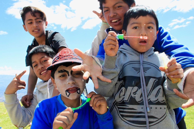 Fünf Buben aus Ecuador schauen in die Kamera und machen Faxen oder spielen.