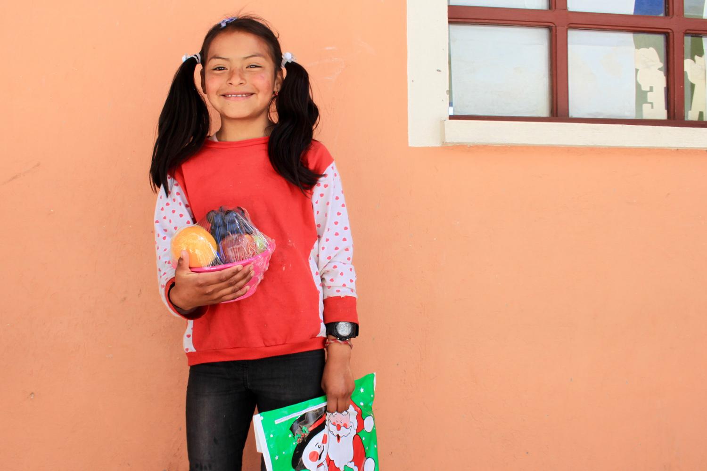 Ein ecuadorianisches Mädchen steht lachend vor einer lachsfarbenen Hauswand mit Geschenken in den Armen.