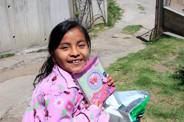 Ein ecuadorianisches Mädchen in einer rosaroten Fliecejacke zeigt stolz ein Tagebuch, das es gerade geschenkt bekommen hat.