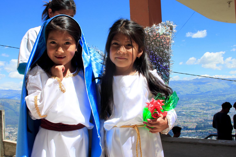 Zwei junge Mädchen aus Ecuadorstehen mit weissen Kleidern und Geschenken in den Händen vor der Kamera.