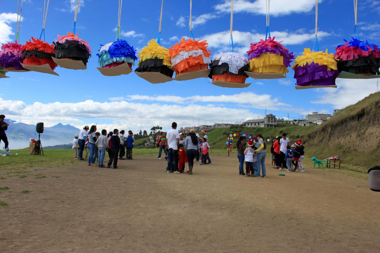 Farbige Pinatas hängen in der Luft. Im Hintergrund sieht man viele Leute, die beisammen stehen und sich unterhalten.