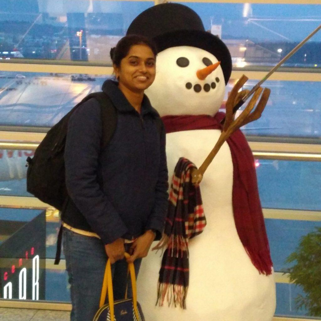 Indische Frau steht vor einem künstlichen Schneemann im Flughafengebäude