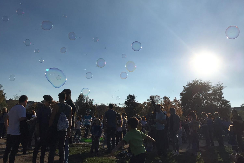 Leute auf einer grünen Wiese. Die Sonne scheint und der Himmel ist strahlend blau. In der Luft sieht man viele Seifenblasen.