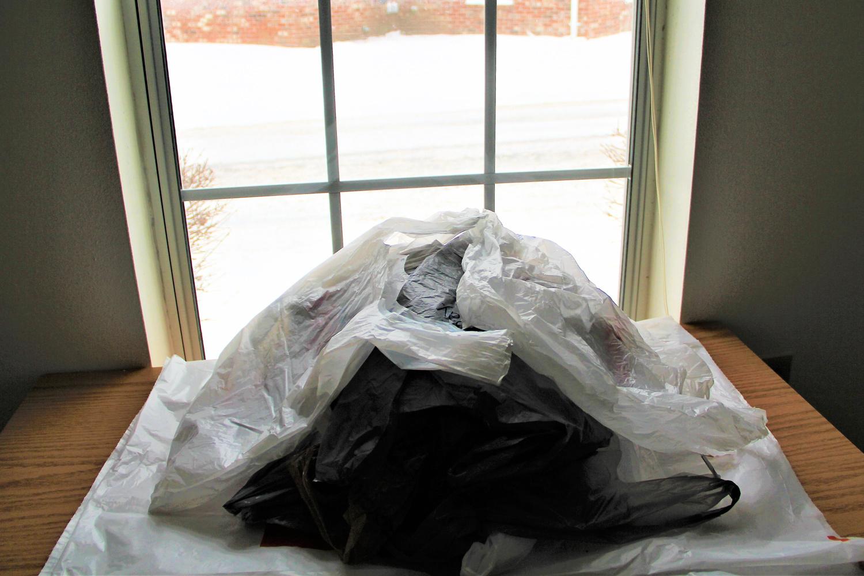 Aufgetürmte schwarze und weisse Plastiksäcke die auf einem Tisch vor einem Fenster liegen.