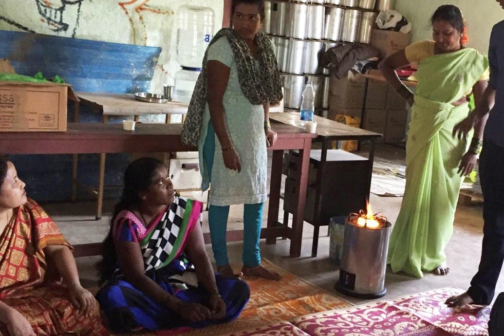 Zwei indische Frauen sitzen im Schneidersitz am Boden, zwei stehen daneben. Vor der einen steht ein kleiner Ofen, bei welchem oben eine Flamme zu sehen ist.