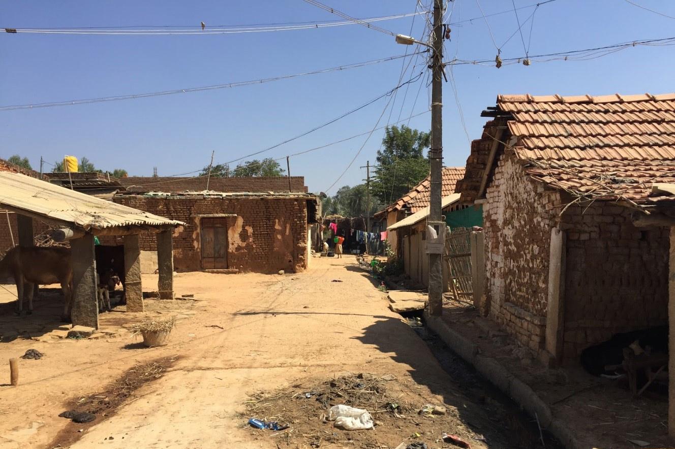 Lehmstrasse in Indien. Die Strasse ist gesäumt von brüchigen Häusern.