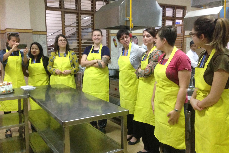 Eine Gruppe von Frauen steht in einem Halbkreis in einer Küche und trägt gelbe Schürzen.