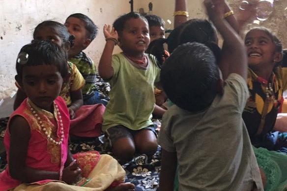 Indische Kinder sitzen am Boden und lächeln.