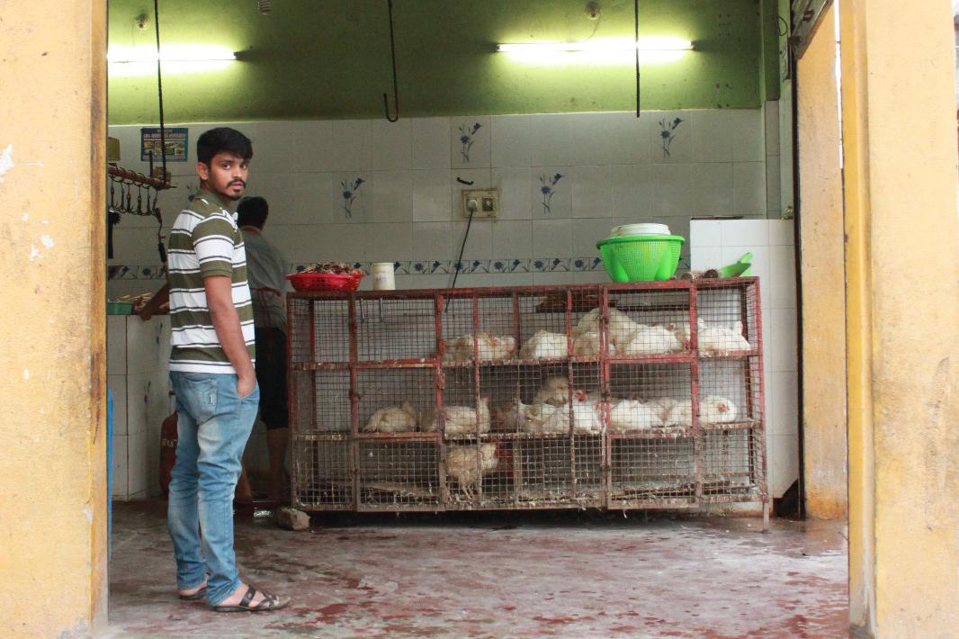 Ein indischer Mann steht vor einem Hühnerkäfig in einer Garage.