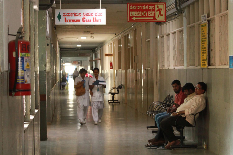 Gang eines Spitals. Zwei Ärzte laufen im Gang, drei Patienten sitzen auf der rechten Seite des Ganges und warten.