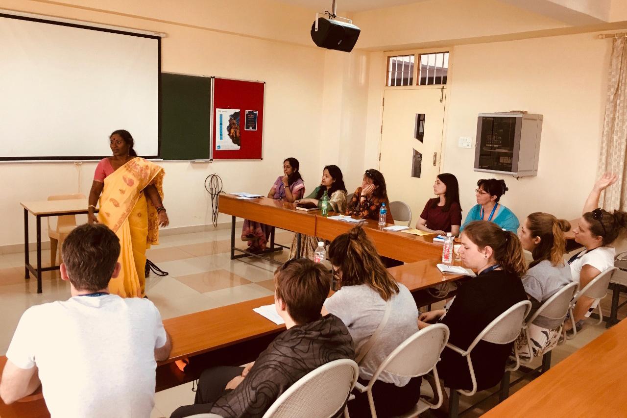 Teilnehmende einer Studienreise sitzen in einem Klassenzimmer. Vorne steht eine indische Frau und präsentiert etwas.