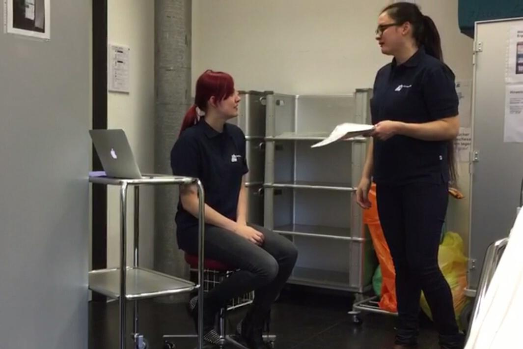 Zwei junge Frauen sprechen miteinander. Die eine sitzt auf einem Hocker, daneben ein Laptop. Die andere steht und hält Papiere in der Hand.