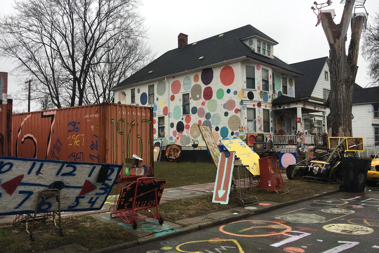 Im Vordergrund sieht man eine farbig bemalte und beschriebene Strasse. Im Hintergrund einen Container und ein gepunktetes Haus.