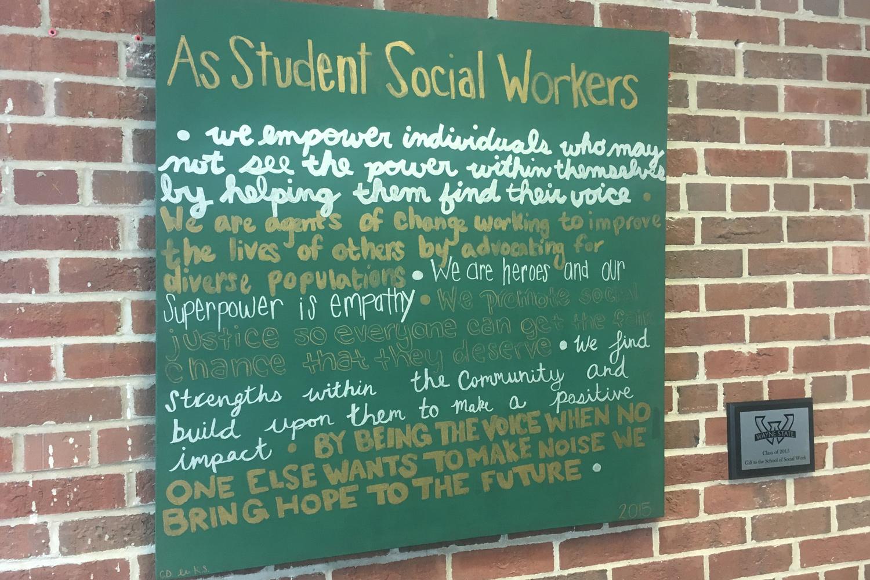 Grünes Plakat das an einer roten Backsteinmauer hängt. Darauf ist mit goldenem und weissem Filzstift geschrieben.
