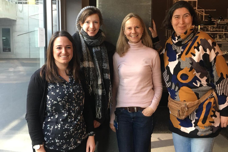 Vier Frauen stehen lächelnd vor einer Betonsäule und posieren für ein Foto.