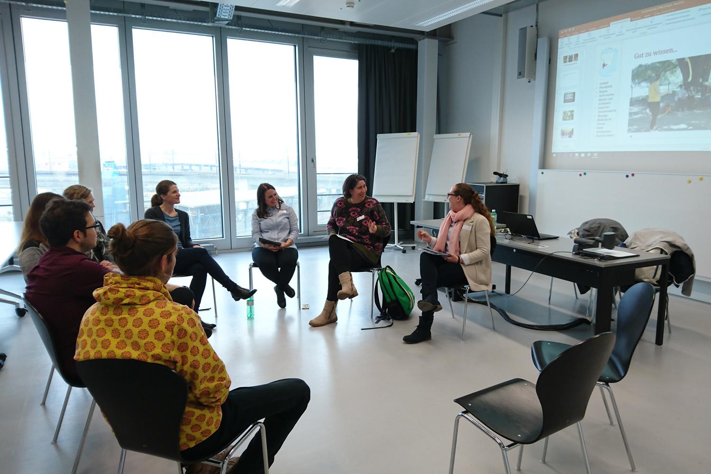 Studierende und Mitarbeitende sitzen auf Stühlen in einem Kreis und diskutieren mit einander. Im Hintergrund sieht man einen Slide einer Powerpoint Präsentation.