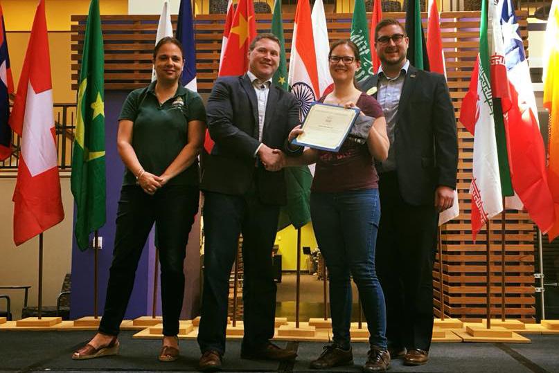 Studierende steht mit dem Diplom in der Hand mit drei weiteren Personen auf einer Bühne. Im Hintergrund stehen Flaggen verschiedener Länder.