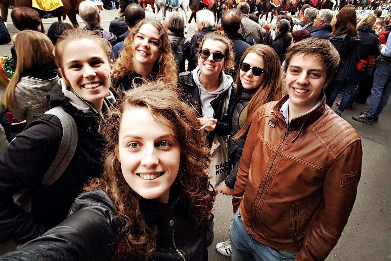 Porträt von sechs Studierenden die in einer Menschenmenge stehen und in die Kamera lächeln.